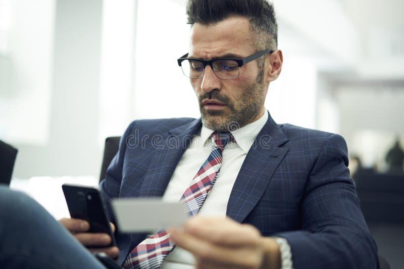 Erwachsener Mann in einer Jacke und in einer Glasfinanzdienstleistung, zum von Berufsanalyse vom Unternehmenseinkommen zu machen stockbilder