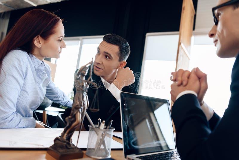 Erwachsener Mann hört auf rothaarige Frau an Rechtsanwalt ` s Schreibtisch, in dem Statue von Themis steht stockfoto