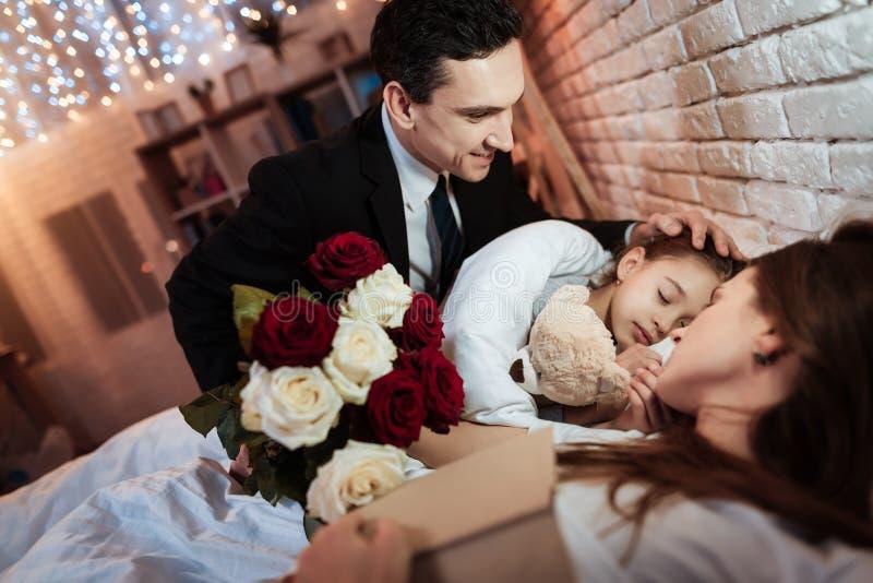 Erwachsener Mann mit Rosenblumenstrauß wird gesetzt, um kleine Tochter zu betten, um zu schlafen Kind schläft stockbilder