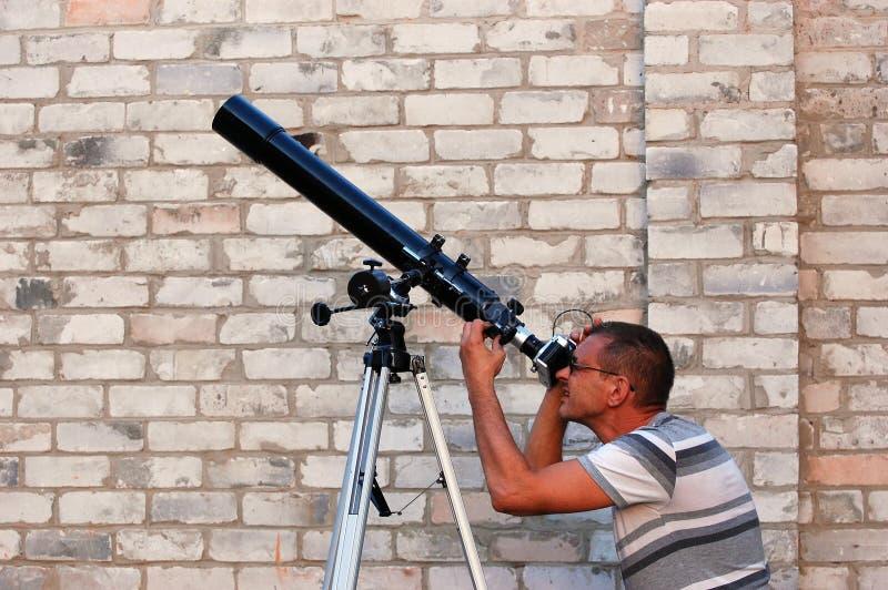 Erwachsener Mann und Teleskop mit Kamera stockfotografie