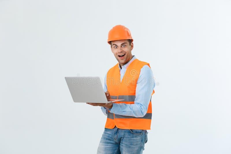 Erwachsener Mannerbauer, der überrascht ist und zuhause mit Laptop im Sturzhelm gearbeitet ist lizenzfreie stockfotografie