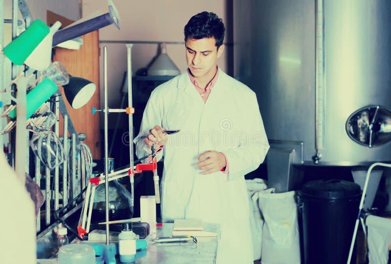 Erwachsener Mannes-laboratorian Arbeiten mit Wein lizenzfreie stockbilder