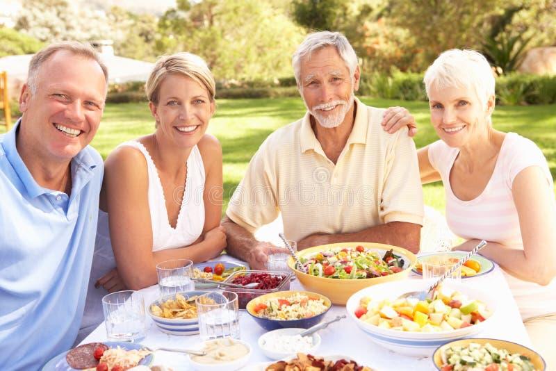 Erwachsener Sohn und Tochter, die Mahlzeit im Garten genießt stockbilder