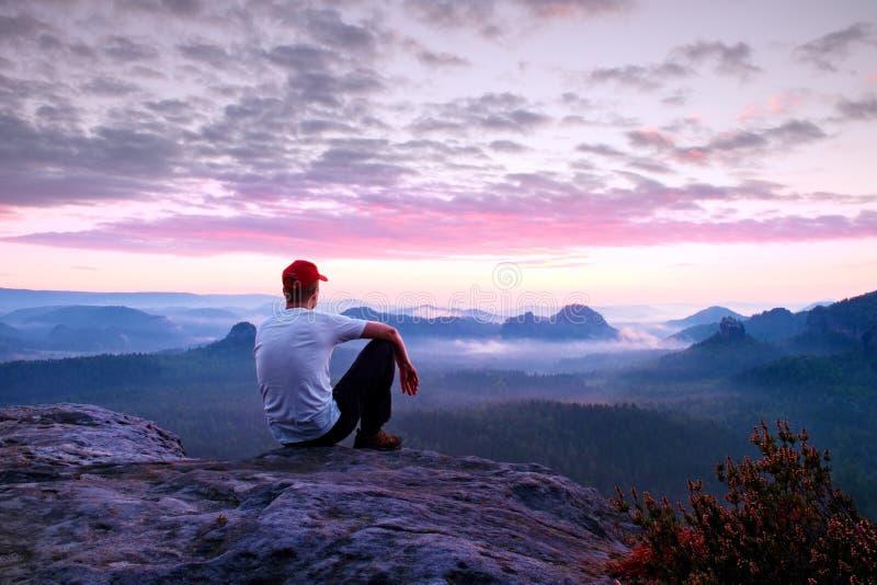 Erwachsener Sportler im weißen Hemd, in den dunklen trousars und in der roten Kappe Mann des kurzen Haares des Ingwers sitzen auf stockfotos