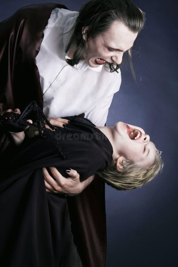 Erwachsener Vampir und sein junges Opfer stockfoto