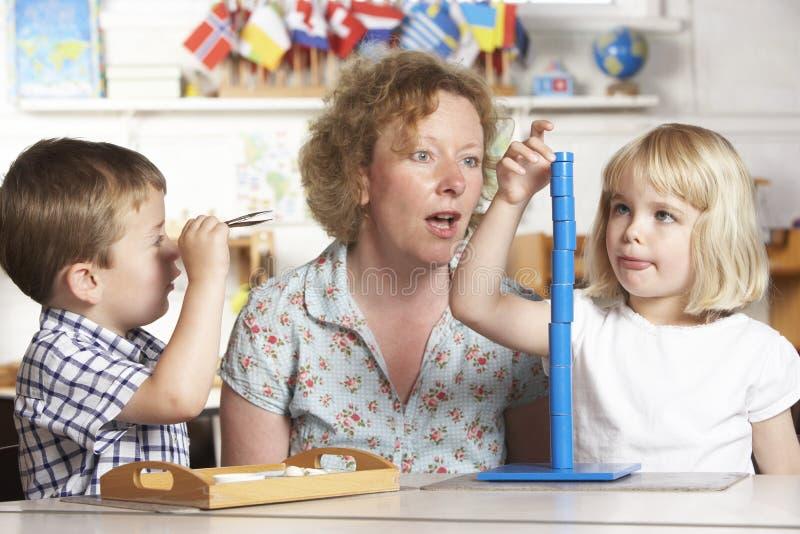 Erwachsener, welche zwei jungen Kindern bei Montessori/vor hilft lizenzfreie stockfotos
