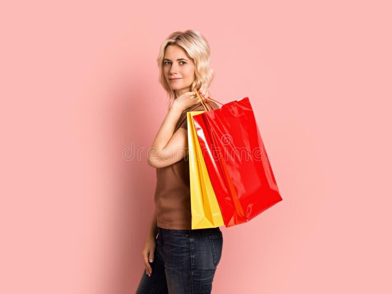Erwachsenes attraktives schönes lächelndes Porträt der Blondine, kaukasisches Mädchen mit Einkaufstaschen auf rosa Hintergrund lizenzfreie stockfotografie