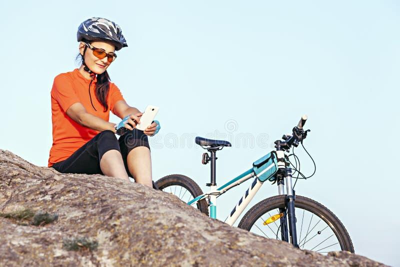Erwachsenes attraktives weibliches Radfahrerstillstehen im Freien, s betrachtend lizenzfreie stockfotos