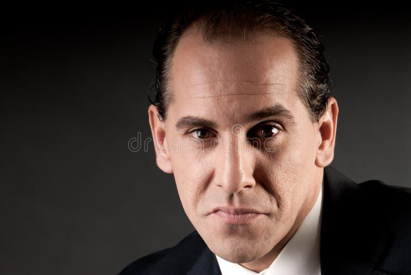 Erwachsenes Geschäftsmannnahaufnahmeportrait auf Dunkelheit lizenzfreies stockbild
