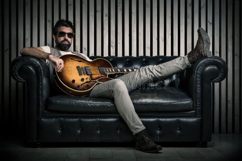 Erwachsenes kaukasisches Gitarristporträt mit der E-Gitarre, die auf Weinlesesofa sitzt Musiksängerkonzept auf Couch und lizenzfreies stockbild