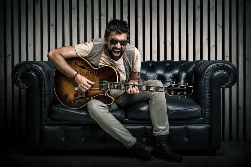 Erwachsenes kaukasisches Gitarristporträt, welches die E-Gitarre sitzt auf Weinlesesofa spielt Musiksängerkonzept auf Couch und lizenzfreie stockbilder
