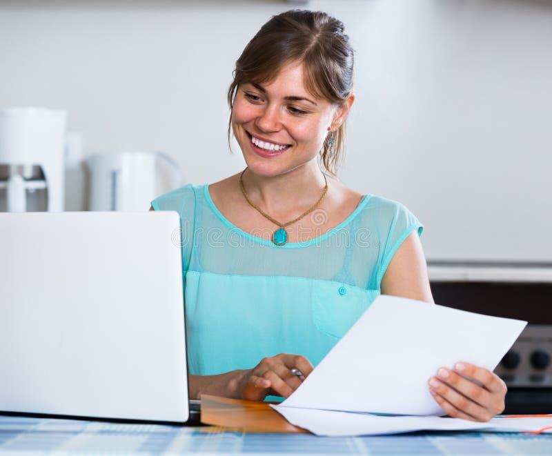 Erwachsenes Mädchen, das zu Hause Darlehen von Kreditinstituten beantragt lizenzfreies stockfoto