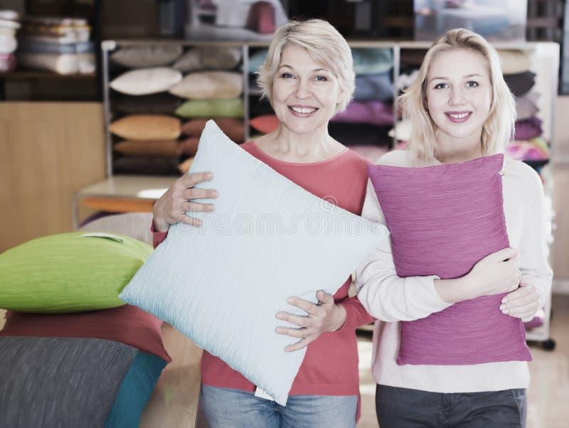 Erwachsenes Mädchen und Mutter, die gekaufte Kissen genießt stockfoto