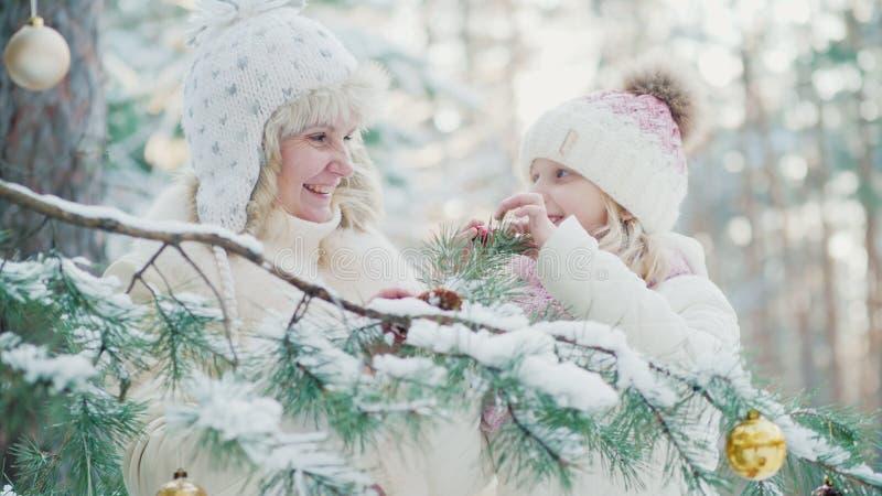 In Erwartung des Weihnachten verzieren Mutter und ein kleines Mädchen im Yard des Hauses einen Weihnachtsbaum mit Spielzeugbällen stockfoto