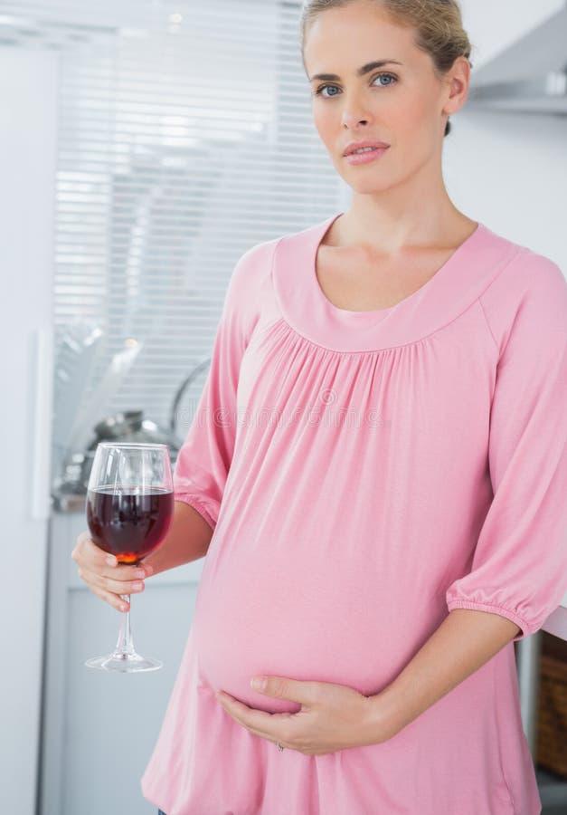 Erwartung die Frau, die Glas Rotwein isst lizenzfreie stockfotos