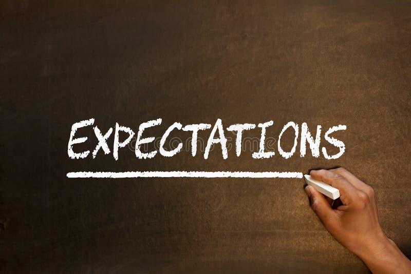 Erwartungen fassen auf Tafel ab stockbilder