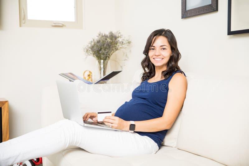 Erwartungsvolle Frau, die Kreditkarte und Laptop für das on-line-Einkaufen verwendet lizenzfreie stockfotografie