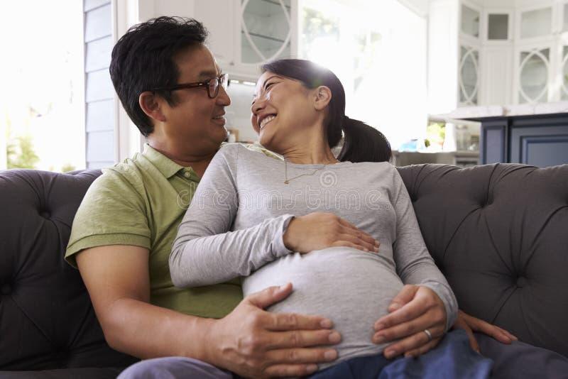 Erwartungsvolle Paare, die auf Sofa At Home Together sich entspannen stockbild