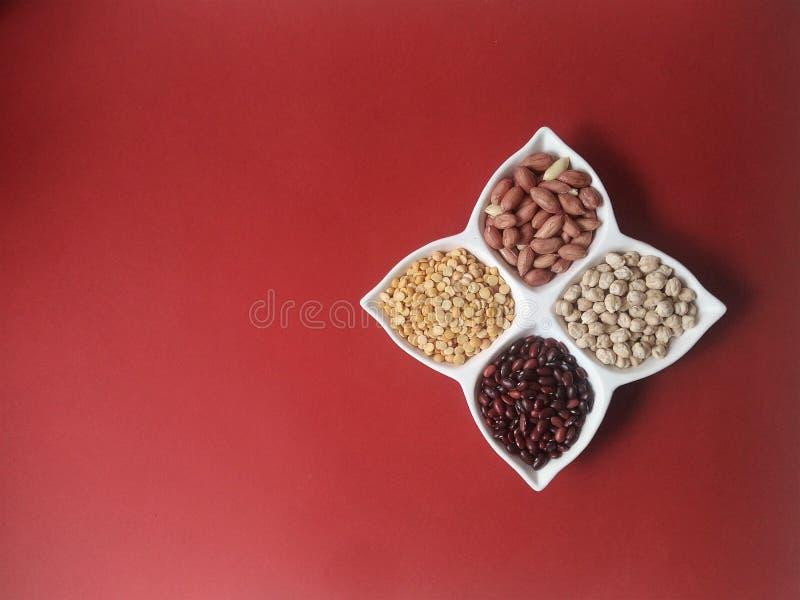 Erwten, bonen, kekers en pinda's in een komblad op een rode achtergrond stock foto