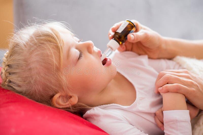 Erziehen Sie das Geben ihrem kranken Kind von Medizintropfen lizenzfreies stockfoto