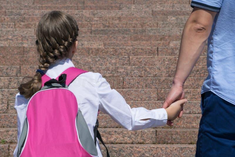 Erziehen Sie führende Tochter zur Schule auf Klassenzimmer, hintere Ansicht gegen Hintergrund der Treppe stockbild