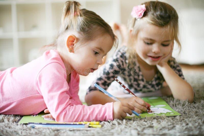 Erziehen Sie zu Hause Zwei kleine Mädchen stockbilder