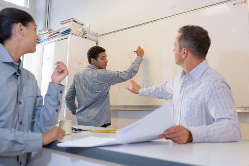 Erzieher, der Lehrling erklärt, Schreiben einzustellen lizenzfreie stockbilder