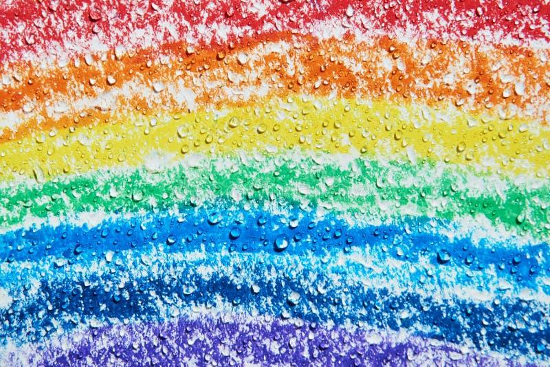 Es gibt die Wassertropfen, die über einem Regenbogen mit Zeichenstiften tropfen lizenzfreie stockfotografie