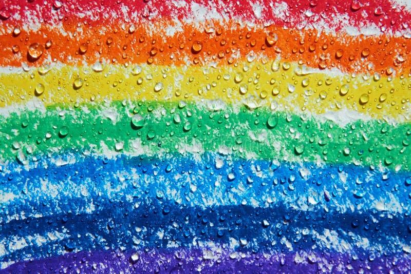 Es gibt die Wassertropfen, die über einem Regenbogen mit Zeichenstiften tropfen lizenzfreies stockfoto