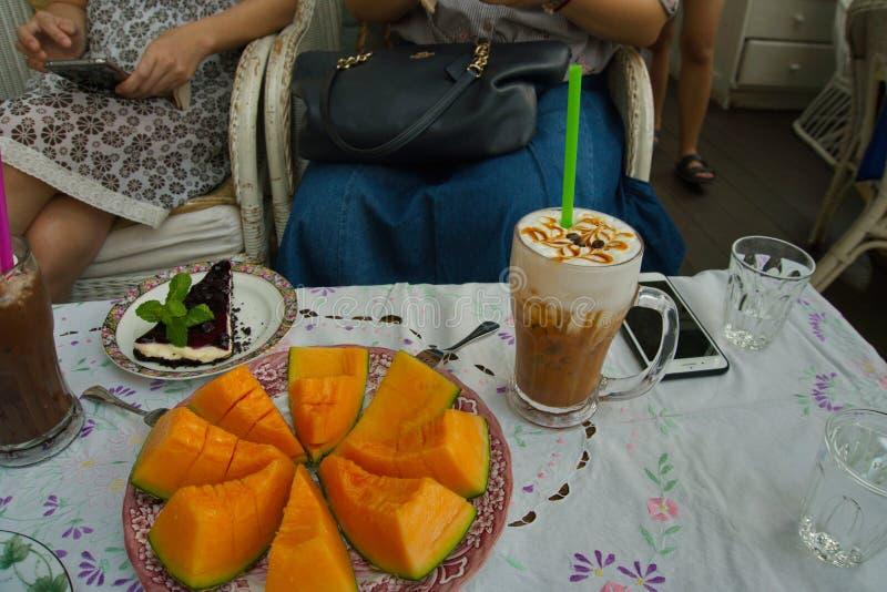 Es gibt Kantalupenmelonenscheiben, ein Glas Eis-Karamell Latte-Kaffee und ein St?ck Blaubeerk?sekuchen sind- auf dem Tisch stockbild
