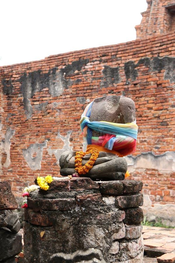 Es gibt keinen von altem Stein-Buddha unvollständigen und alten Kopf, Anbetung durch buntes Gewebe und Blume in den Ruinen und bl stockfoto