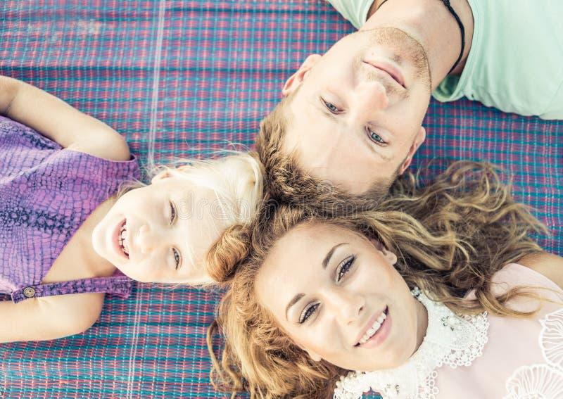 Es gibt 3 Mädchen und ihre Mutter, die auf der orange Couch sitzen stockfotos