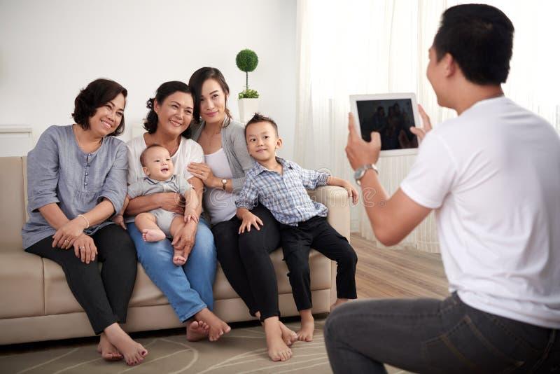 Es gibt 3 Mädchen und ihre Mutter, die auf der orange Couch sitzen lizenzfreie stockbilder