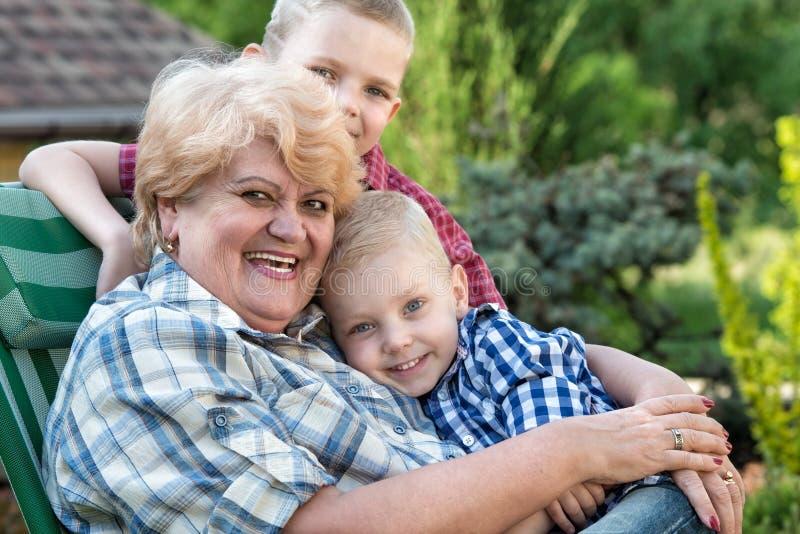 Es gibt 3 M?dchen und ihre Mutter, die auf der orange Couch sitzen Schöne Großmutter und ihre zwei geliebten Enkelkinder lizenzfreie stockfotografie