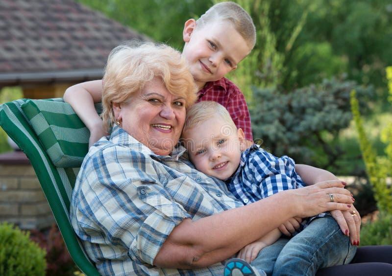 Es gibt 3 M?dchen und ihre Mutter, die auf der orange Couch sitzen Schöne Großmutter und ihre zwei geliebten Enkelkinder lizenzfreie stockbilder