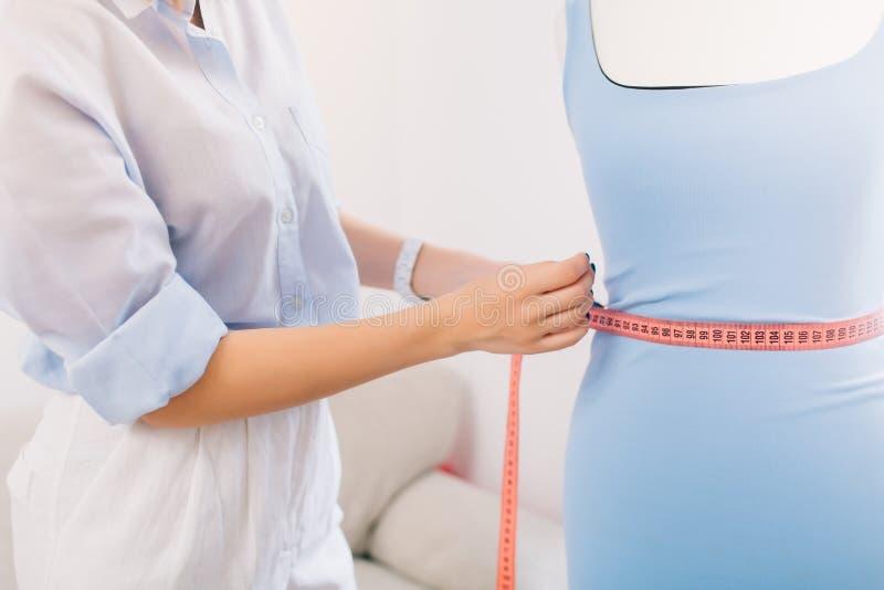 Es ist ein Bild, in dem die Hauptsache auf Hände eines Mädchens konzentriert wird, das Installation vom Kleid auf dem Mannequin h stockfoto