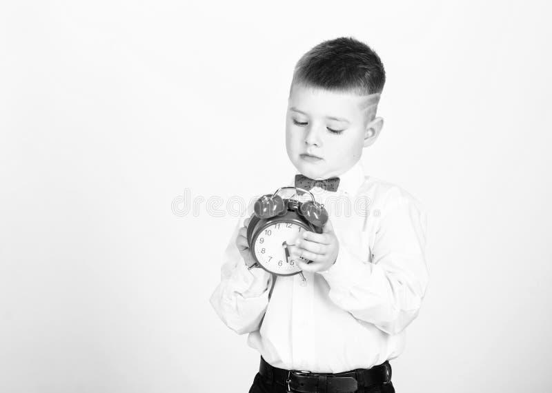 Es ist Zeit Zeitplan und TIMING Morgenprogramm Sch?ler mit Wecker Hemdes des Kinderrote Fliege des entz?ckenden Jungen wei?en lizenzfreie stockbilder