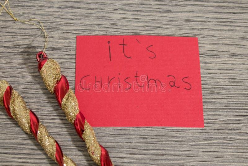 Es la Navidad escribe en un papel rojo con las decoraciones imagenes de archivo