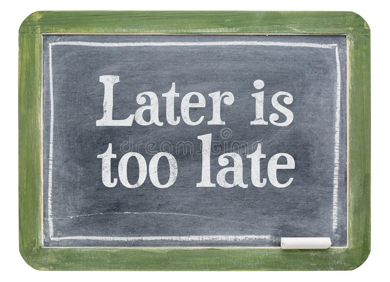 Es más adelante demasiado atrasado - el texto de motivación en la pizarra fotos de archivo