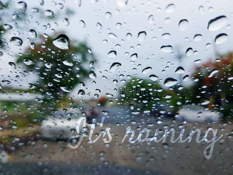 Es regnet die Texte, die auf Blurred Hintergrund von Regen-Tröpfchen auf Spiegel überlagert werden stockfoto
