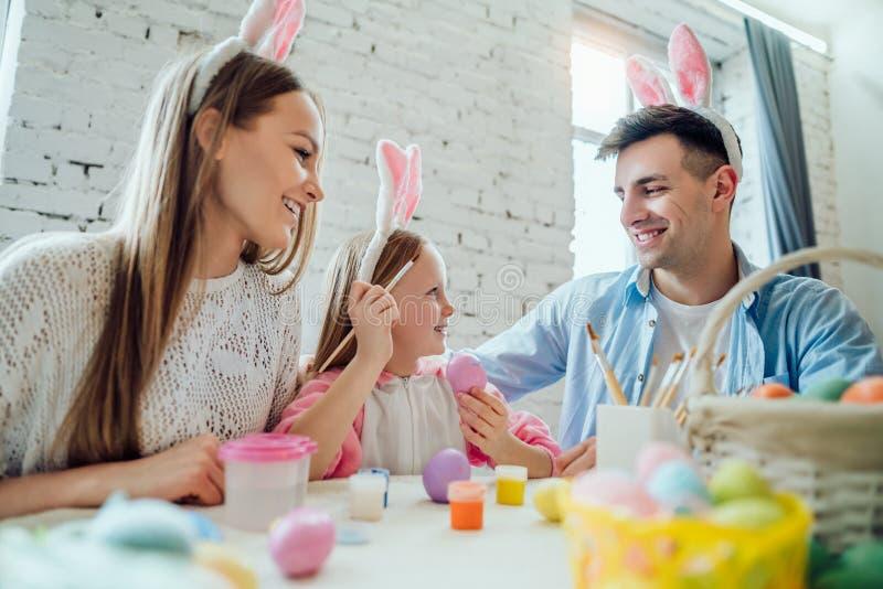 Es tan interesante pintar los huevos de Pascua con su familia Huevos de Pascua felices de la pintura de la familia junto foto de archivo