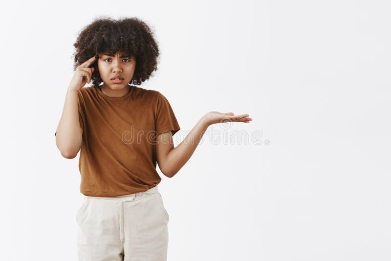 Es usted mudo o estúpido Retrato de la mujer afroamericana preguntada enfadada y cabreada con el encogimiento afro del peinado foto de archivo