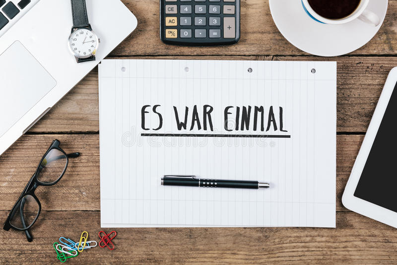 Es war einmal, German text for Once Upon a Time on note pad at o. Es war einmal, German text for Once Upon a Time, on note pad at office desk with electronic royalty free stock images