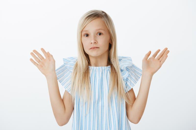 Es war nicht ich, ich ist unschuldig Porträt des verwirrten nervösen kleinen blonden Mädchens, das Palmen anhebt, oben in der Aus stockbilder