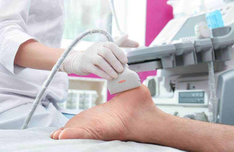 Esame ecografico di conduzione di medico del piede del paziente in clinica immagine stock libera da diritti