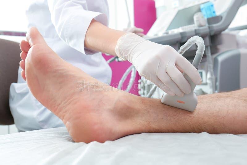 Esame ecografico di conduzione di medico della gamba del paziente in clinica fotografia stock libera da diritti