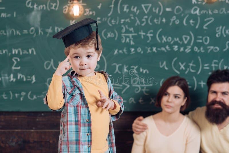 Esame ed esame Il ragazzino pensa sulla domanda dell'esame Bambino in cappuccio di graduazione pronto per esame focused fotografia stock libera da diritti