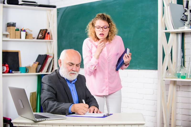 Esami Studiare con le moderne tecnologie studente e insegnante di scuola superiore con laptop studentessa con tutore alla lavagna immagine stock