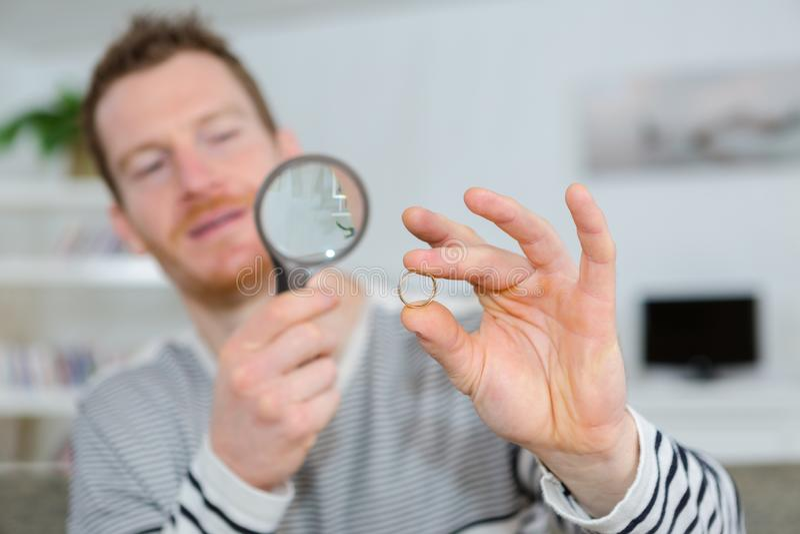 Esaminando anello facendo uso della lente d'ingrandimento fotografia stock libera da diritti