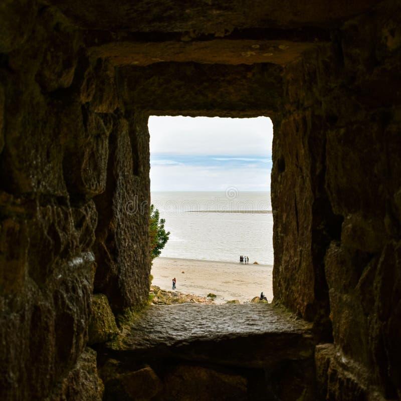 Esaminando il mare ed il cielo blu attraverso una finestra di pietra Sensazione di speranza fotografia stock libera da diritti